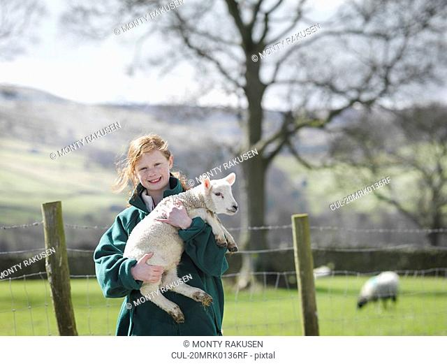 Child holding lamb smiling