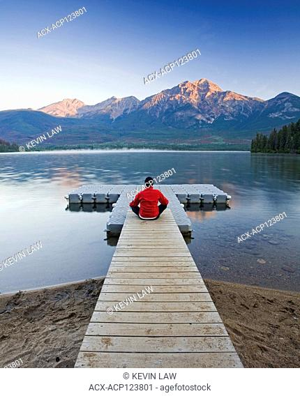Man sitting on dock meditating at Pyramid Lake, Jasper National Park, Alberta, Canada