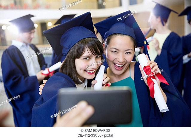 Smiling female college graduates in cap and gown taking selfie