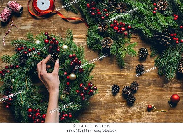top view of florist hand making Christmas wreath on wooden tabletop