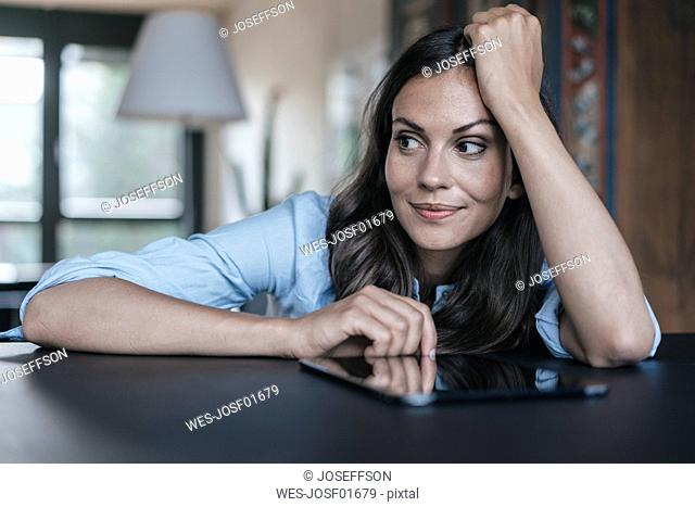 Woman with tablet leaning on table