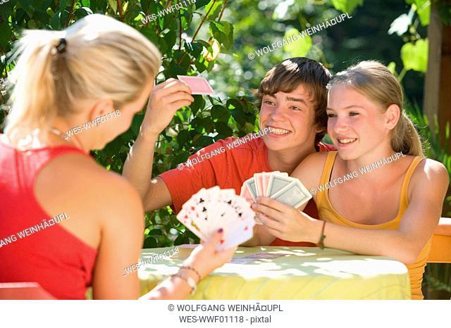 Austria, Salzburger Land, Teenagers 14-15 playing cards in garden