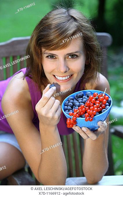 woman sitting in the garden eating blueberries