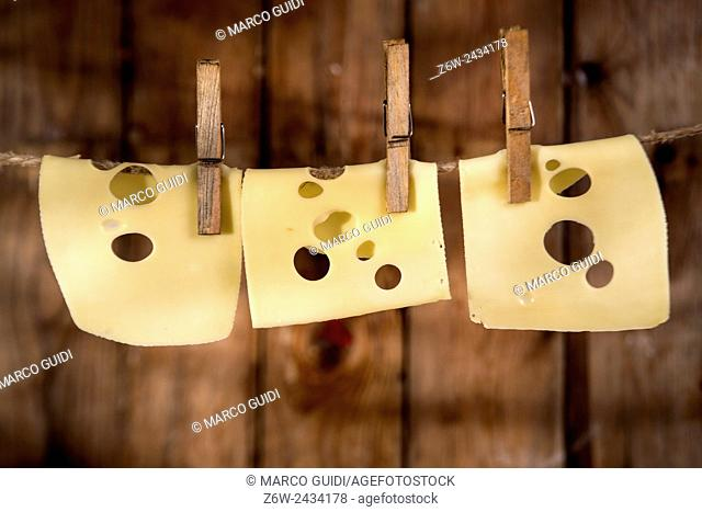 Presentation of slices of Swiss cheese Emmentaler hanging by a thread