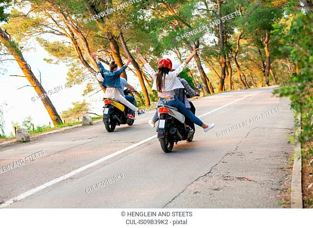 Rear view of two couples riding mopeds on rural road, Split, Dalmatia, Croatia