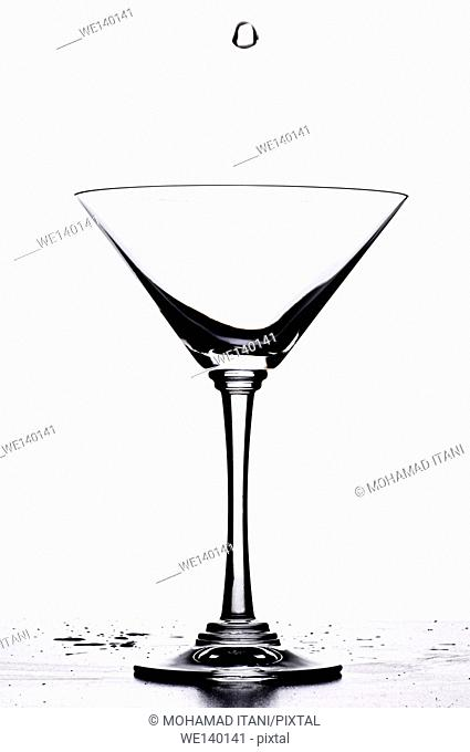 single drop of water falling into an empty glass on a white background