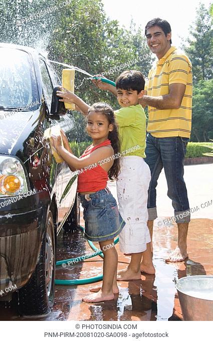 Man and his children washing a car, New Delhi, India