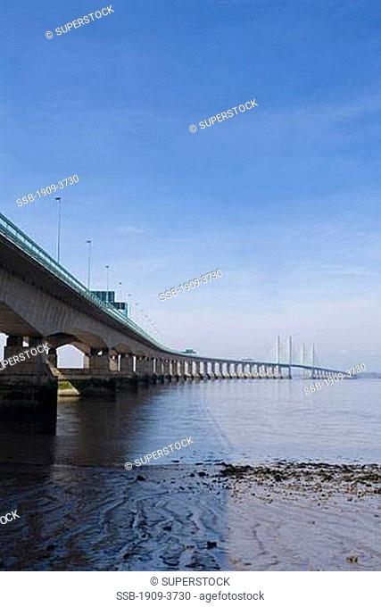 New Severn Suspension Bridge across the River Severn estuary that divides England from Wales on sunny spring day with blue sky Gloucester Gloucestershire Glos...
