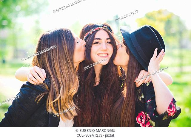 Portrait of three stylish young female friends kissing on cheek in park