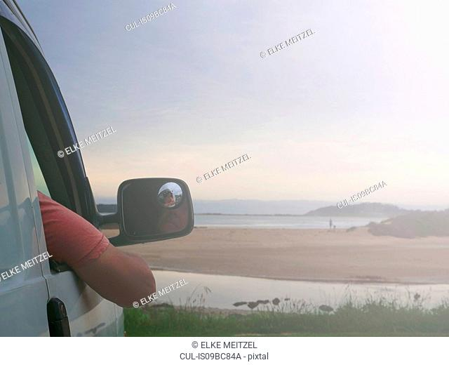 Senior man sitting in car, looking at coastal view, Broulee, New South Wales, Australia