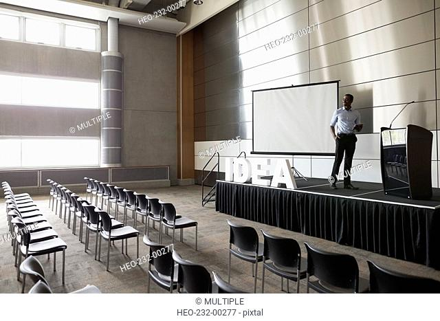Man standing on stage in empty auditorium