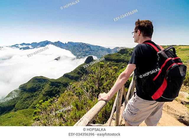 A man standing on a viewpoint above clouds and admiring a spectacular view from Paul da Serra plateau over Pico Ruivo mountain, in Madeira island, Portugal