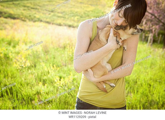 Young woman in a meadow in early summer, holding a dog
