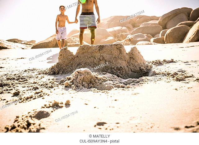 Boy and father strolling on sandcastle beach, Cape Town, South Africa