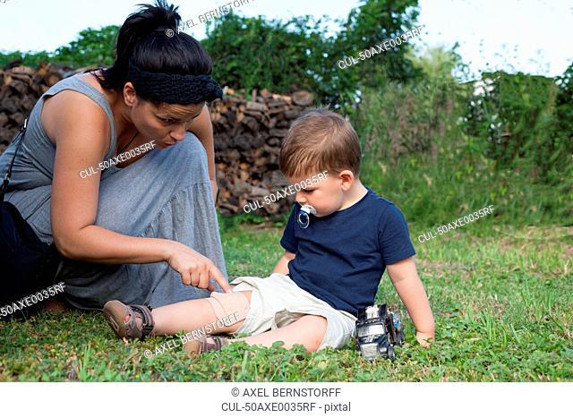 Mother putting bandage on boys knee