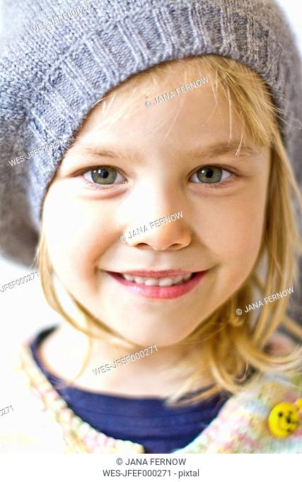 Portrait of smiling little girl wearing cap