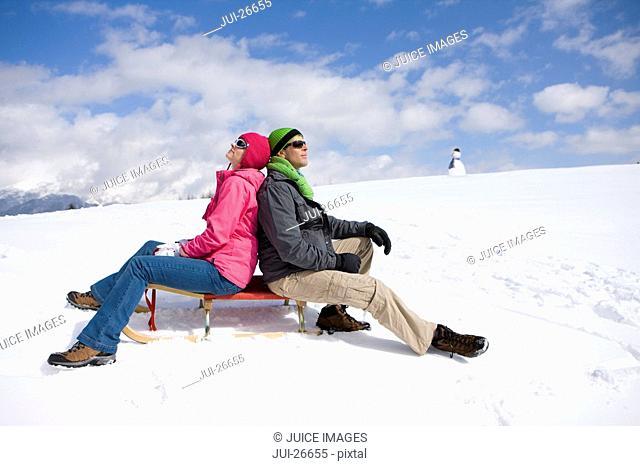 Smiling couple sitting on sled on snowy ski slope