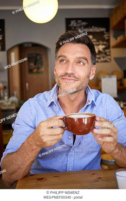 Portrait of smiling man with cup of coffee in a coffee shop