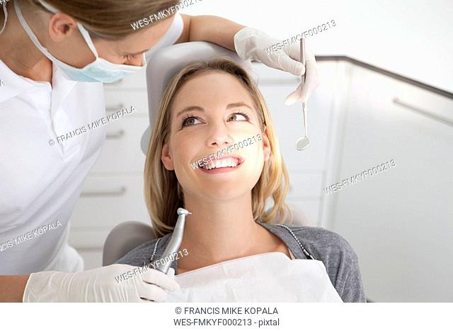 Germany, Young woman getting her teeth examined by dentist