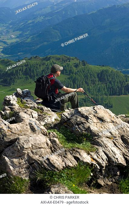 A male hiker enjoys the panoramic view from the Kitzbuheler Horn. Kitzbuehel, Tyrol, Austria
