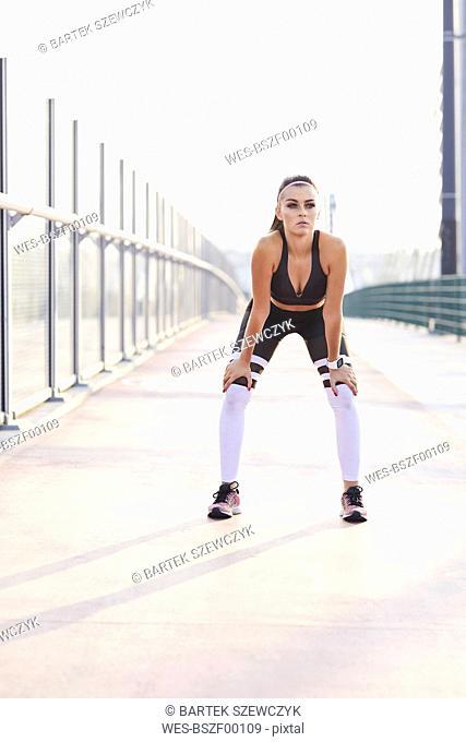 Female runner having break during city workout