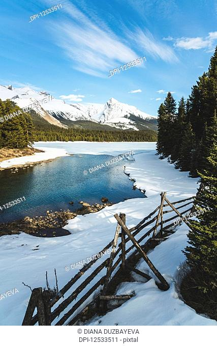 Thawing of a frozen lake and snow-capped rugged mountains peaks, Jasper National Park; Alberta, Canada