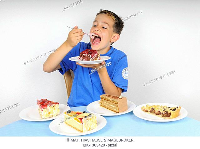 Boy eating cake at a table with four plates with other pieces of cake
