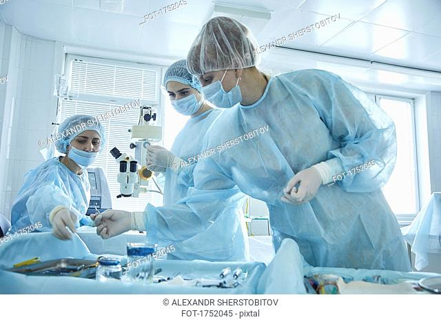Female surgeon passing medical equipment to doctor during surgery at hospital