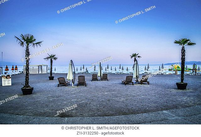 Empty beach chairs with large folded down umbrellas and palm trees line the waterfront at sundown in Opatija on the Adriatic sea in Croatia