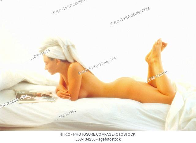 Nude woman reading a magazine