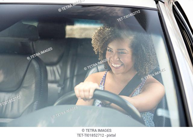 Young woman smiling while driving car