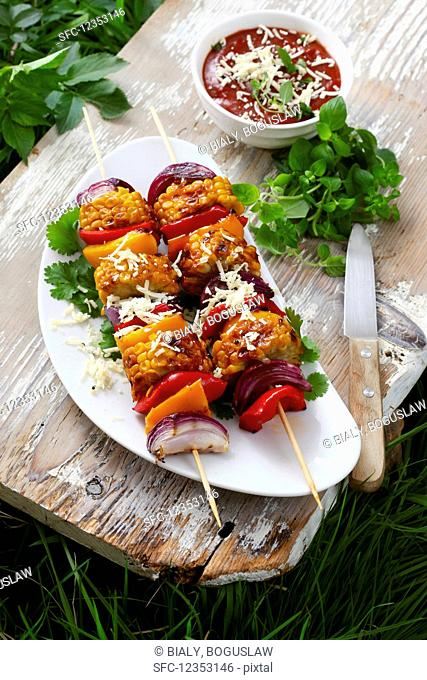 Vegetable skewers topped with grated cheese