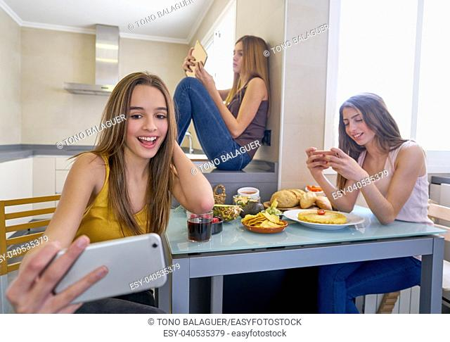 teen girls best friends having lunch eating at kitchen with smartphone