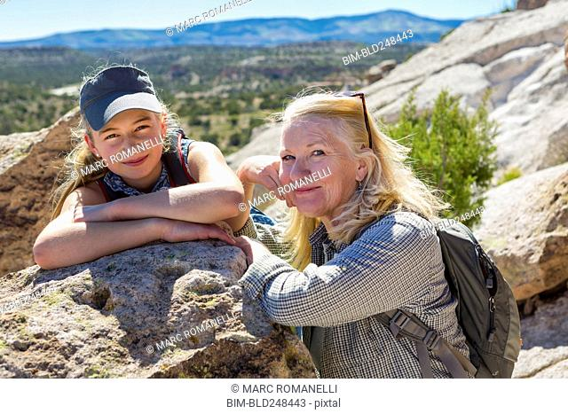 Portrait of Caucasian grandmother and granddaughter leaning on rock