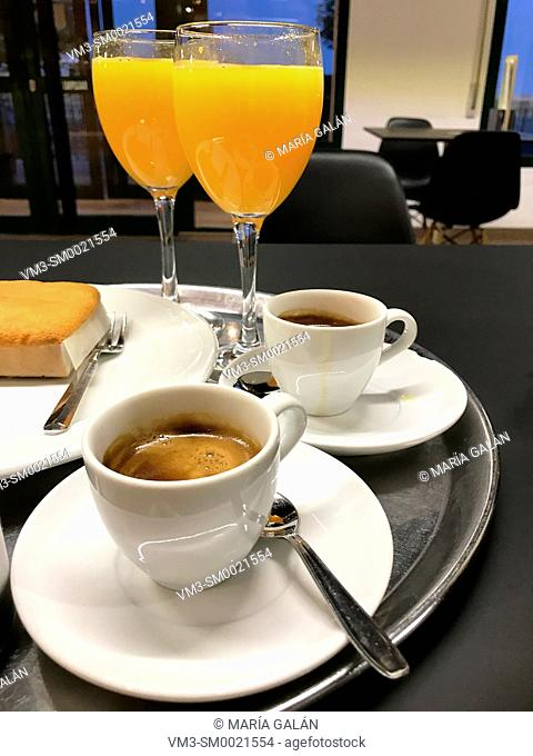 Two cups on coffee, two glasses of orange juice and sobao pasiego on a tray. Spain