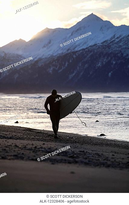 Surfer With His Surfboard At Kachemak Bay, Homer Spit, Southcentral Alaska, USA