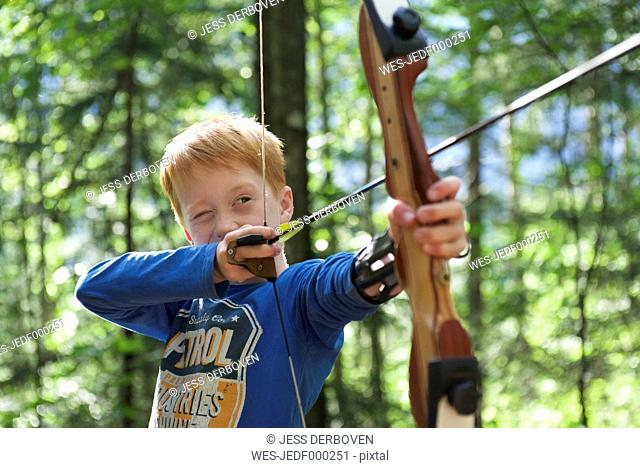 Portrait of a boy with bow and arrow in an adventure park