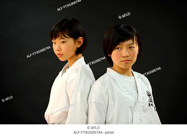 Japanese kids in karate uniform on black background