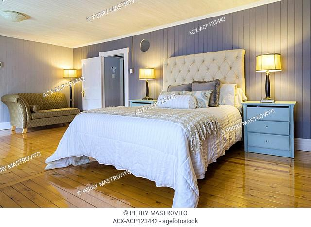 Queen size bed with white bedspread, beige cloth headboard, light blue end tables with drawers and gold and grey upholstered recamier in master bedroom with...