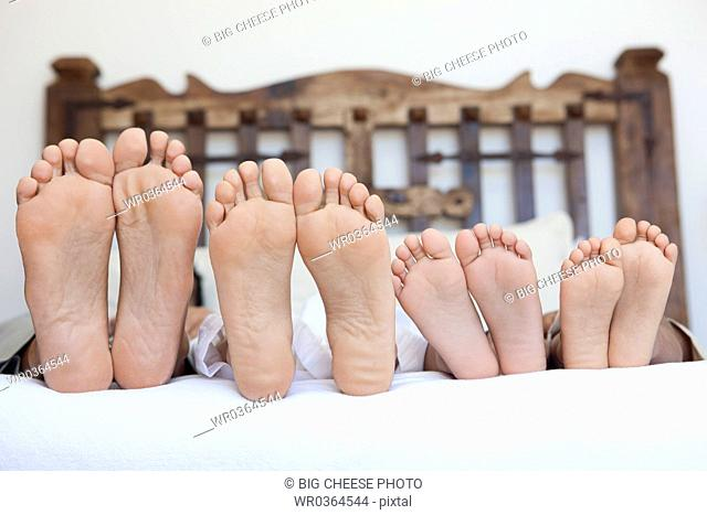 family lying on bed, feet lined up