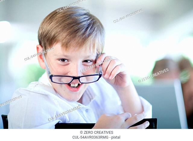 Boy playing businessman at desk
