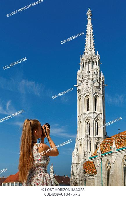 Mid adult woman taking photography of Matthias Church, rear view, Budapest, Hungary