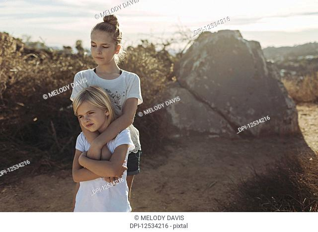 Two sisters stand on hiking trail in an embrace; Los Angeles, California, United States of America