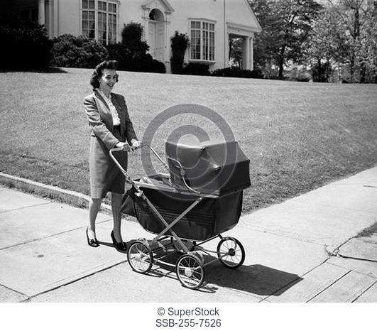 Mid adult woman pushing a baby carriage