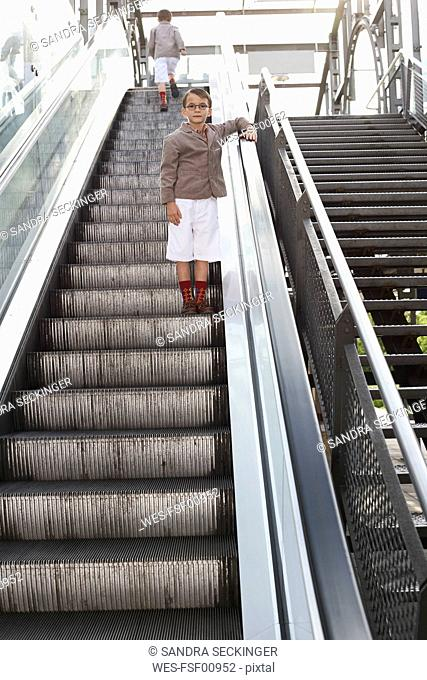Boy standing on escalator while his brother walking away