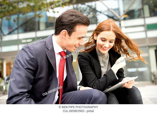 Businesspeople in city using digital tablet