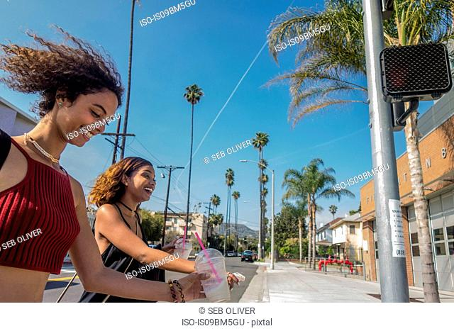 Two young women crossing street, Los Angeles, California, USA
