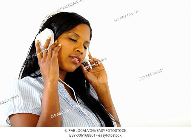Close up portrait of a calm young female listening to music while resting