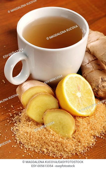Cup of ginger tea and fresh ingredients - ginger, lemon and brown sugar
