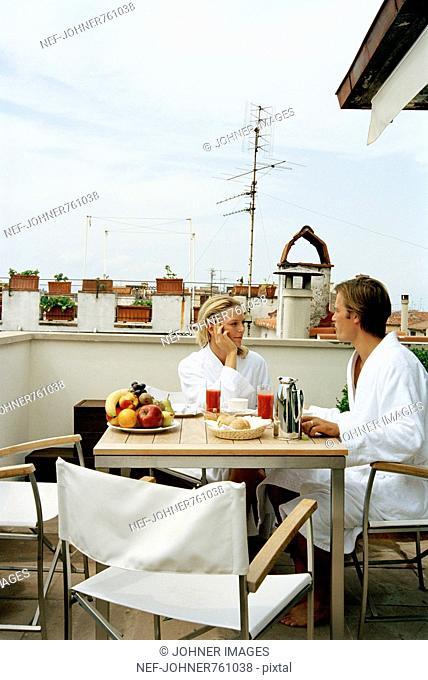 Couple having breakfast on a terrace, Italy